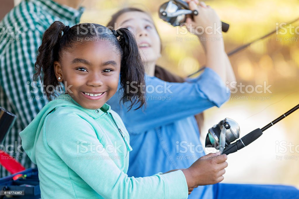 Beautiful African American girl fishes with family stock photo