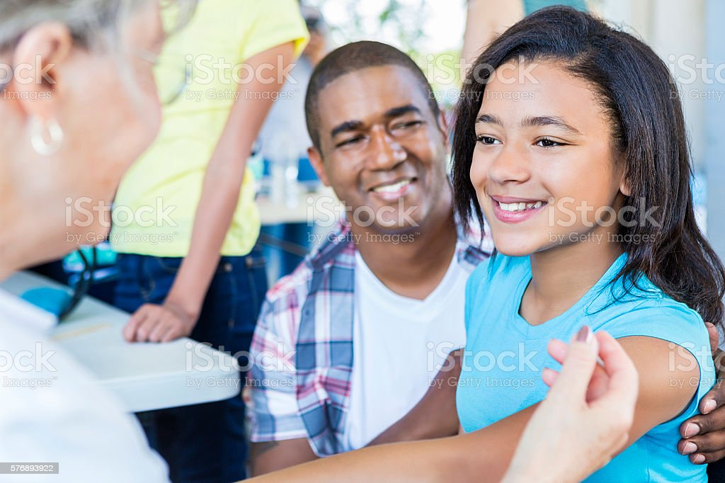 Beautiful African American girl smiling at her doctor stock photo