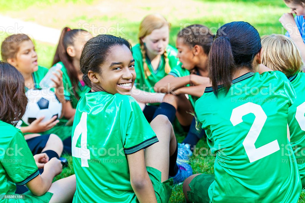 Beautiful African American girl smiling with her soccer team stock photo
