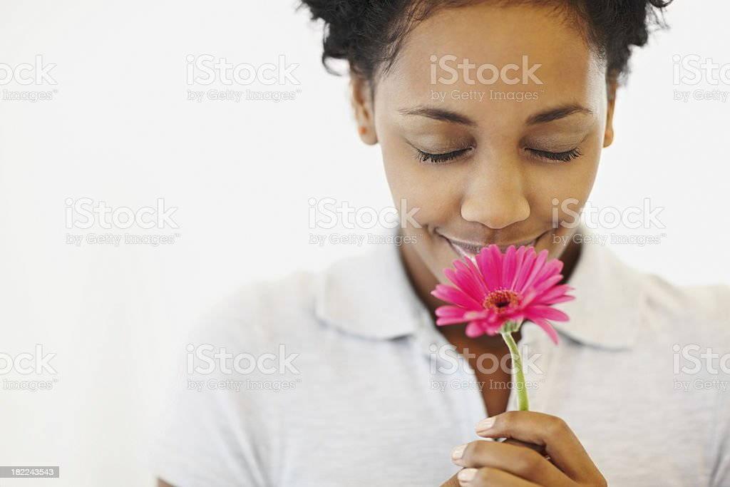 Beautiful African American lady smelling pink flower royalty-free stock photo