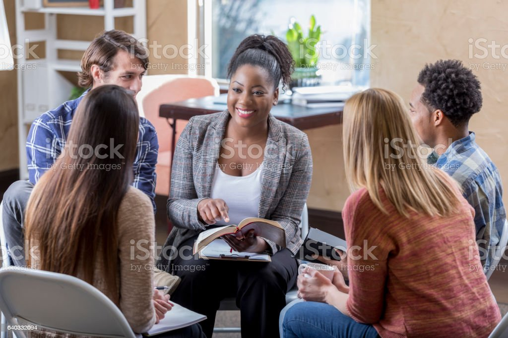 Beautiful African American leads diverse Bible study group stock photo