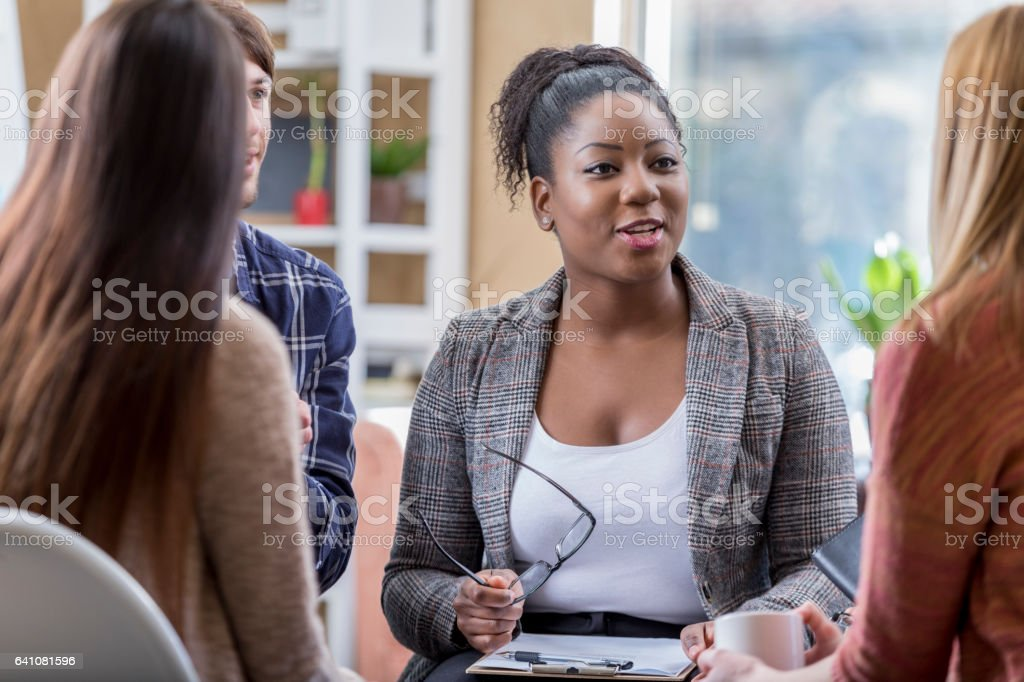 Beautiful African American leads group therapy session stock photo
