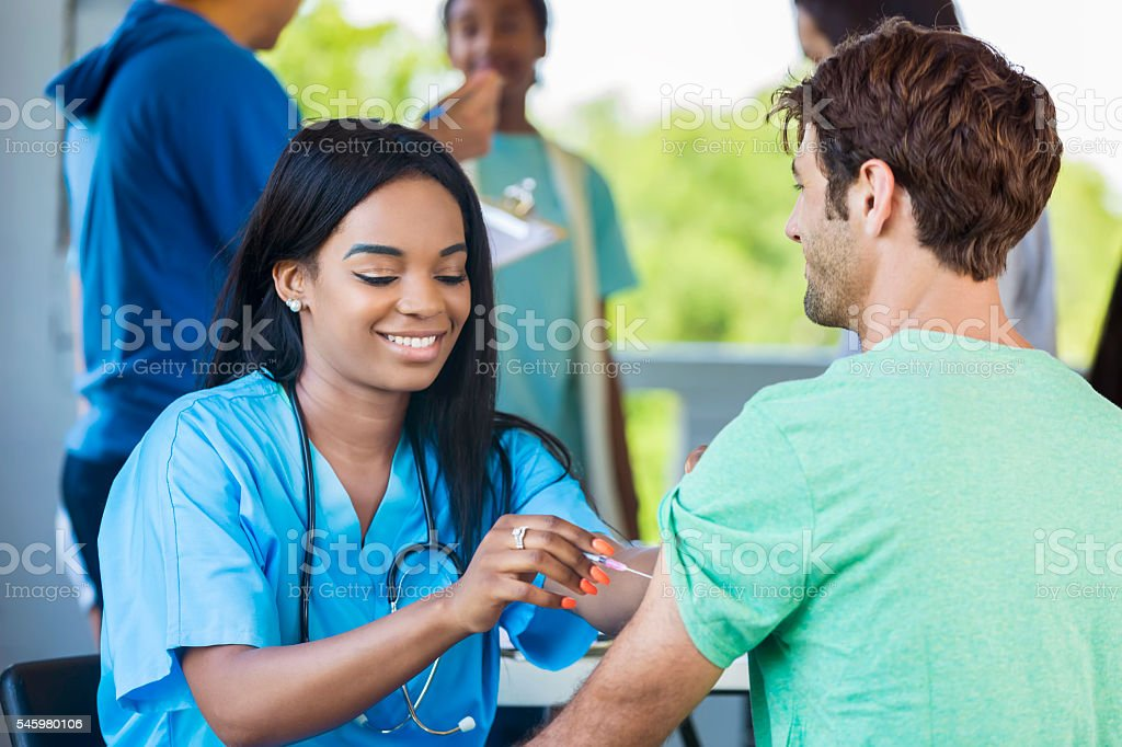 Beautiful African American Nurse administering a vaccination stock photo