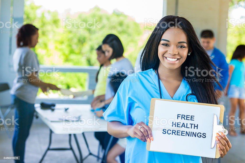 Beautiful African American Nurse holding 'Free Health Screenings' sign stock photo