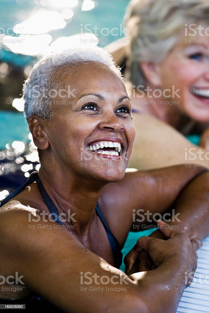 Beautiful African American senior woman in swimming pool laughin royalty-free stock photo