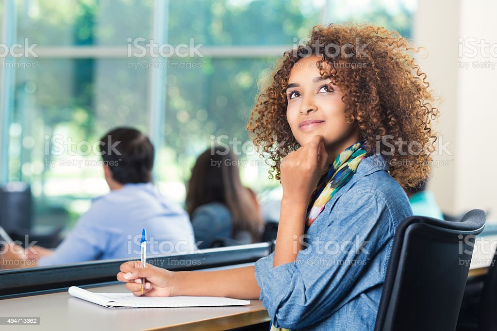 Beautiful African American student thinking during test stock photo