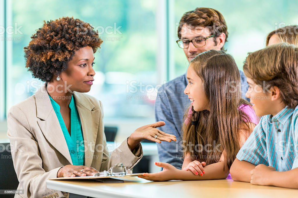 Beautiful African American teacher meets with Family stock photo
