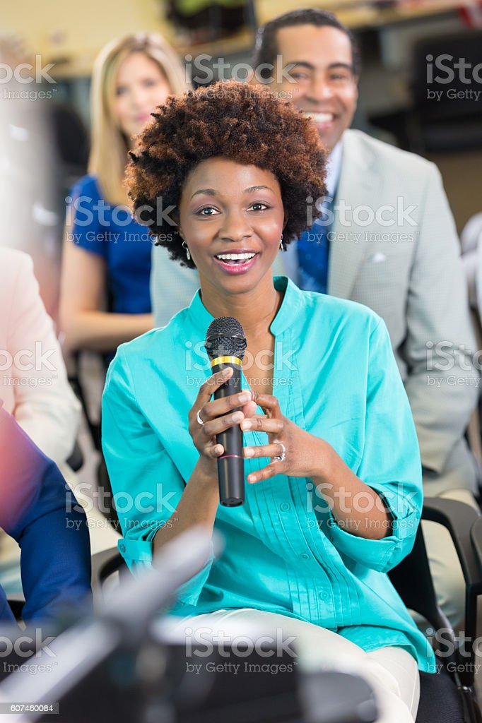 Beautiful African American woman addresses a political candidate during meeting stock photo