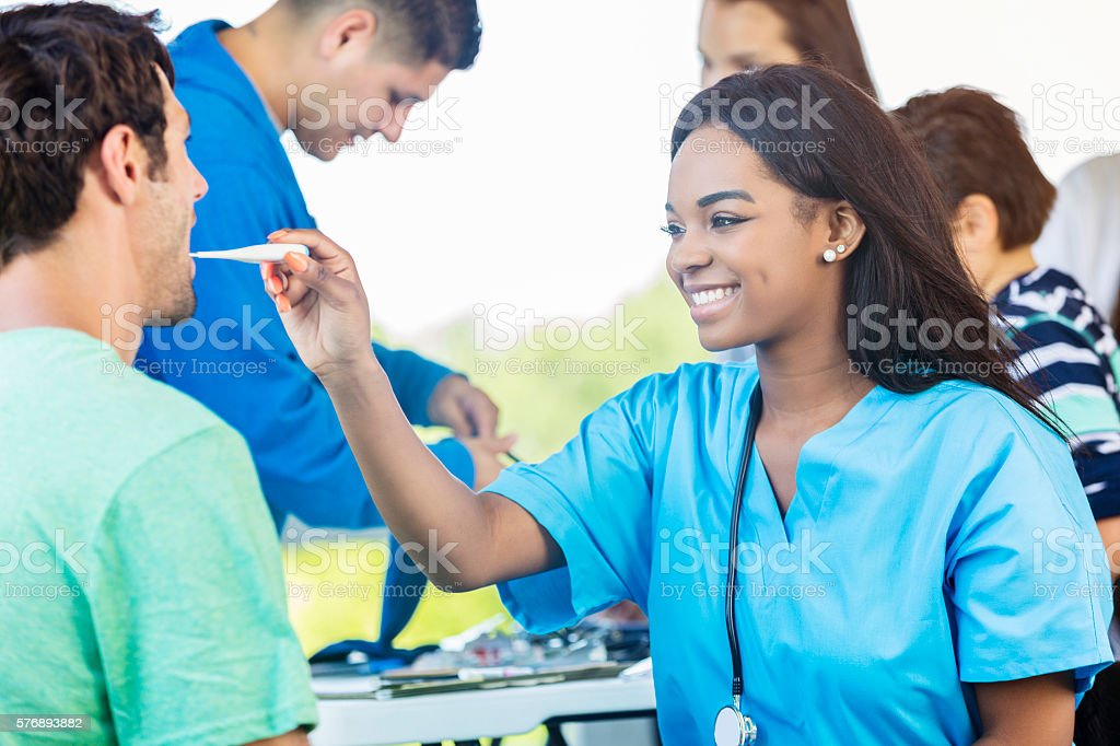 Beautiful African American Woman checking mans temperature stock photo