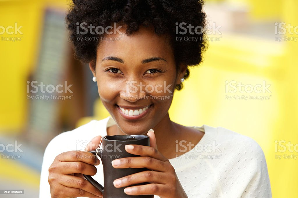 Beautiful african american woman smiling with cup of a coffee stock photo