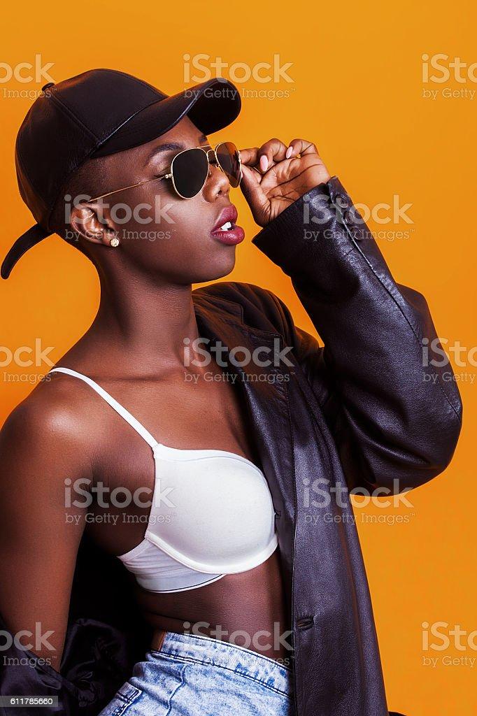 Beautiful african model portrait wearing baseball cap and sunglasses stock photo