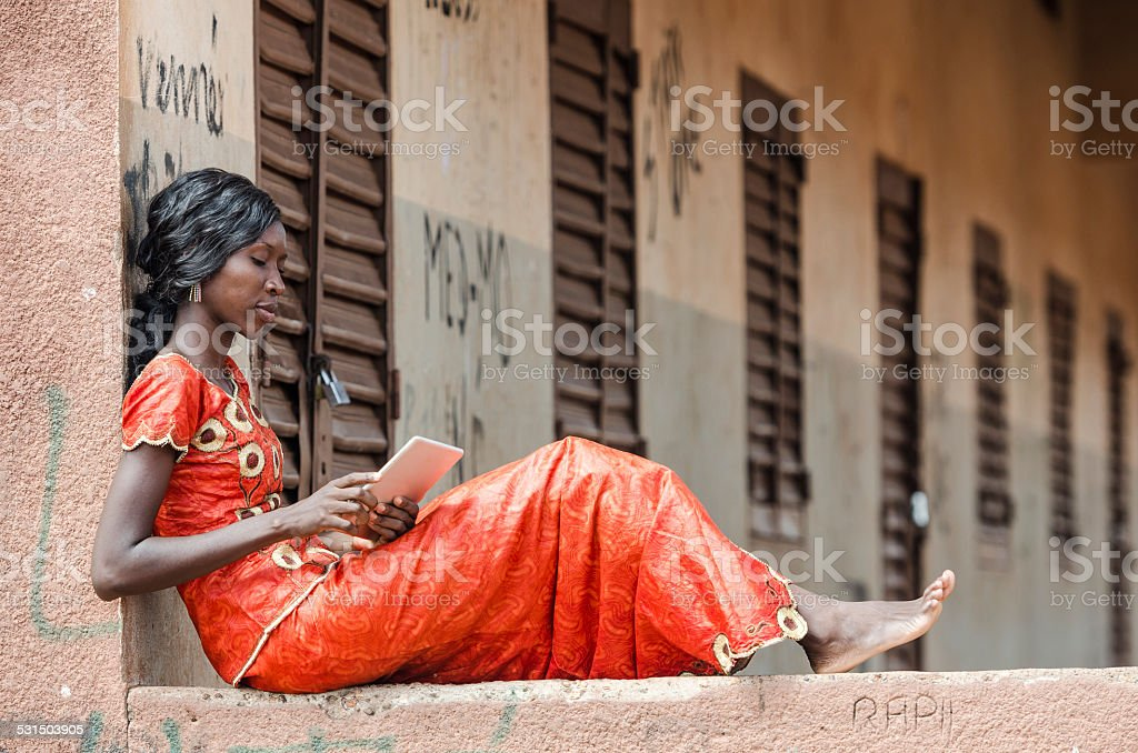 Beautiful African Model Reading Article On Tablet Computer PC stock photo