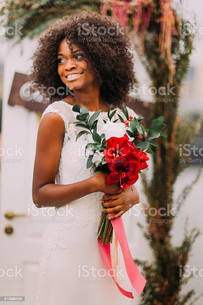 Beautiful african moony bride smiling with bouquet of red flowers stock photo