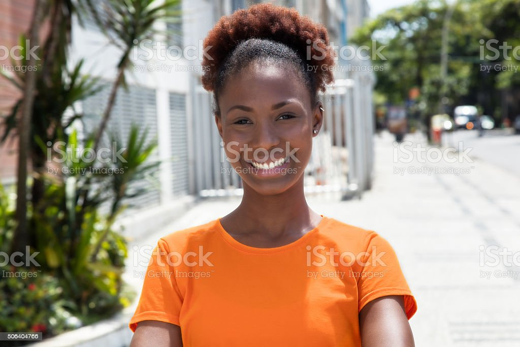 Beautiful african woman in a orange shirt stock photo