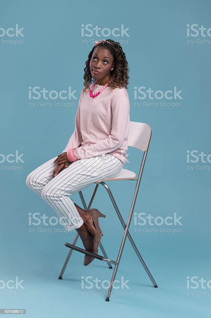 Beautiful african woman sitting on a chair and thinking. stock photo