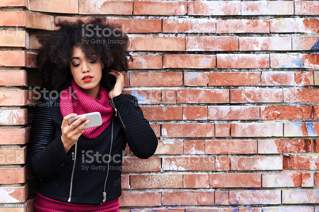 Beautiful african woman using smart phone on street stock photo