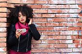 Beautiful african woman using smart phone on street