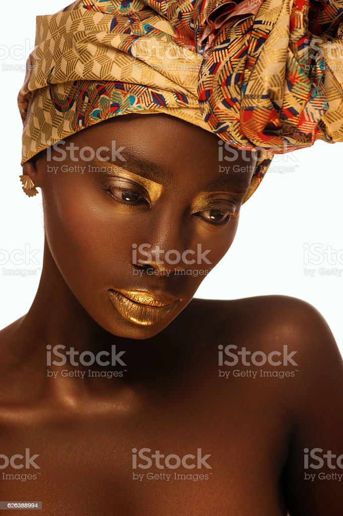 beautiful african woman with creative gold make–up and turban stock photo