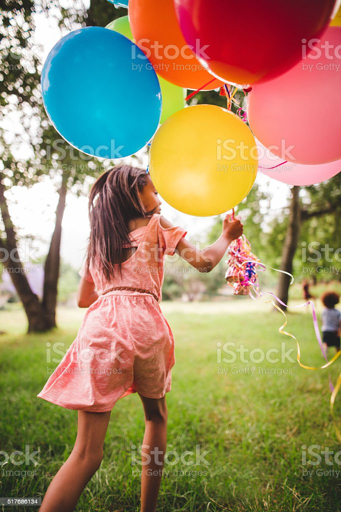 Beautiful African-American girl running in the park stock photo