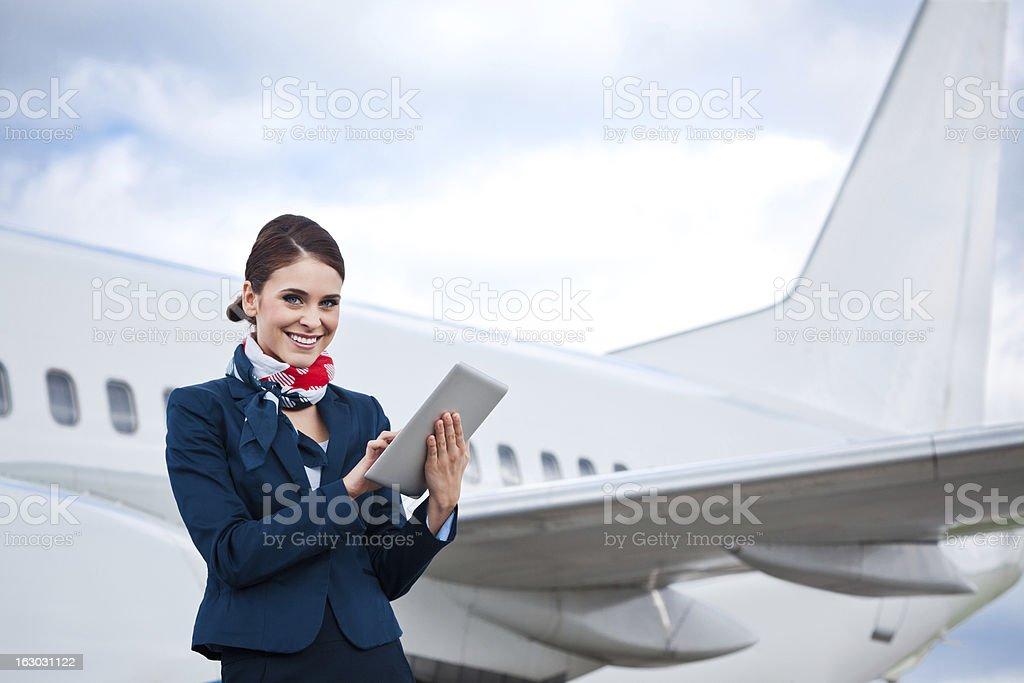 Beautiful air stewardess with digital tablet stock photo