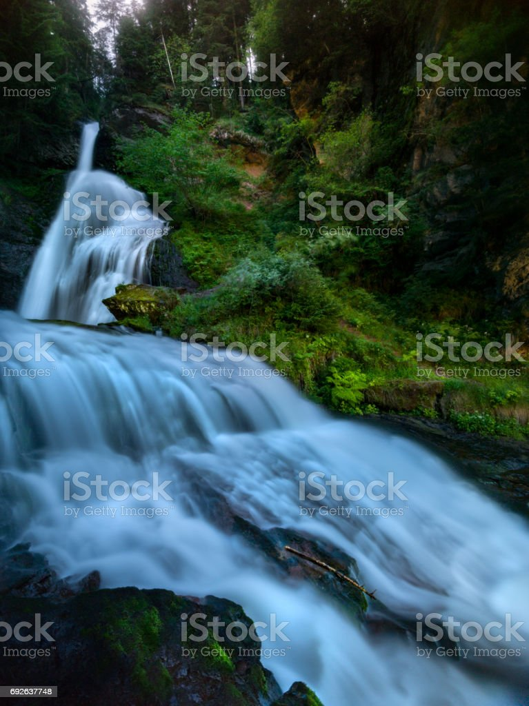 Beautiful alpine waterfall at sunset stock photo