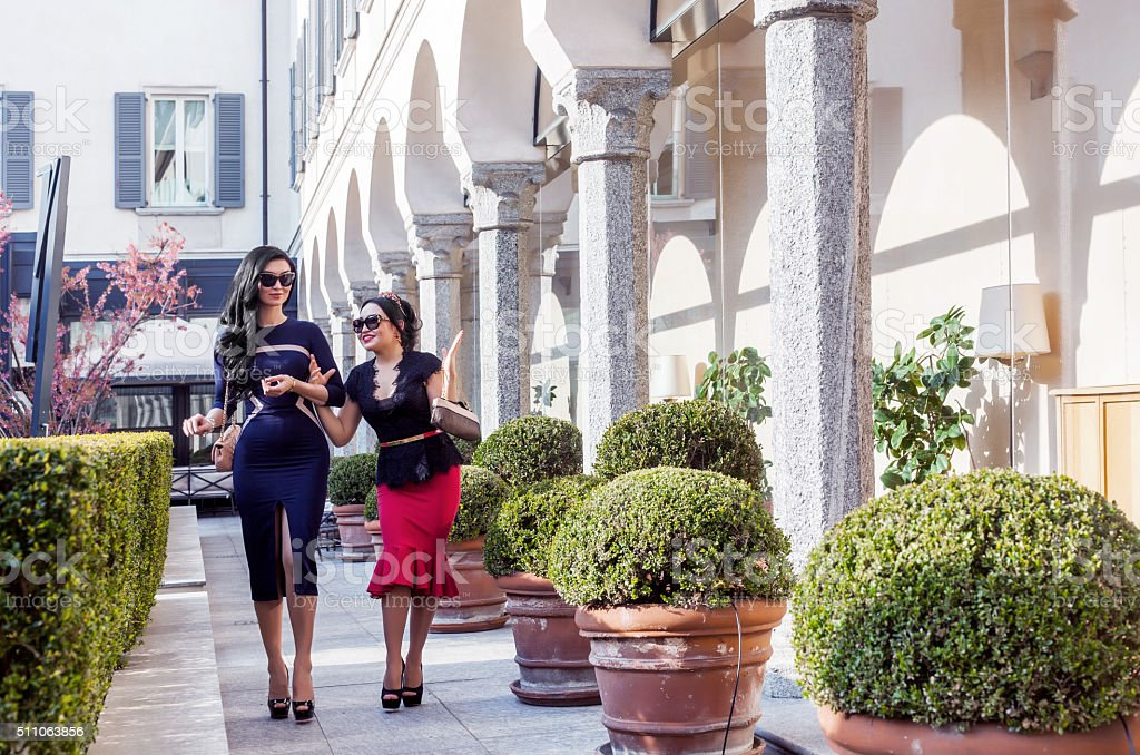 Beautiful and elegant women walking and talking near colonnade stock photo