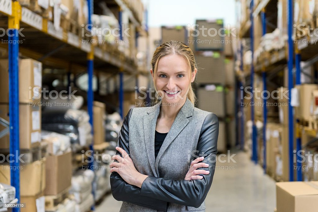 Beautiful and happy female boss in warehouse stock photo