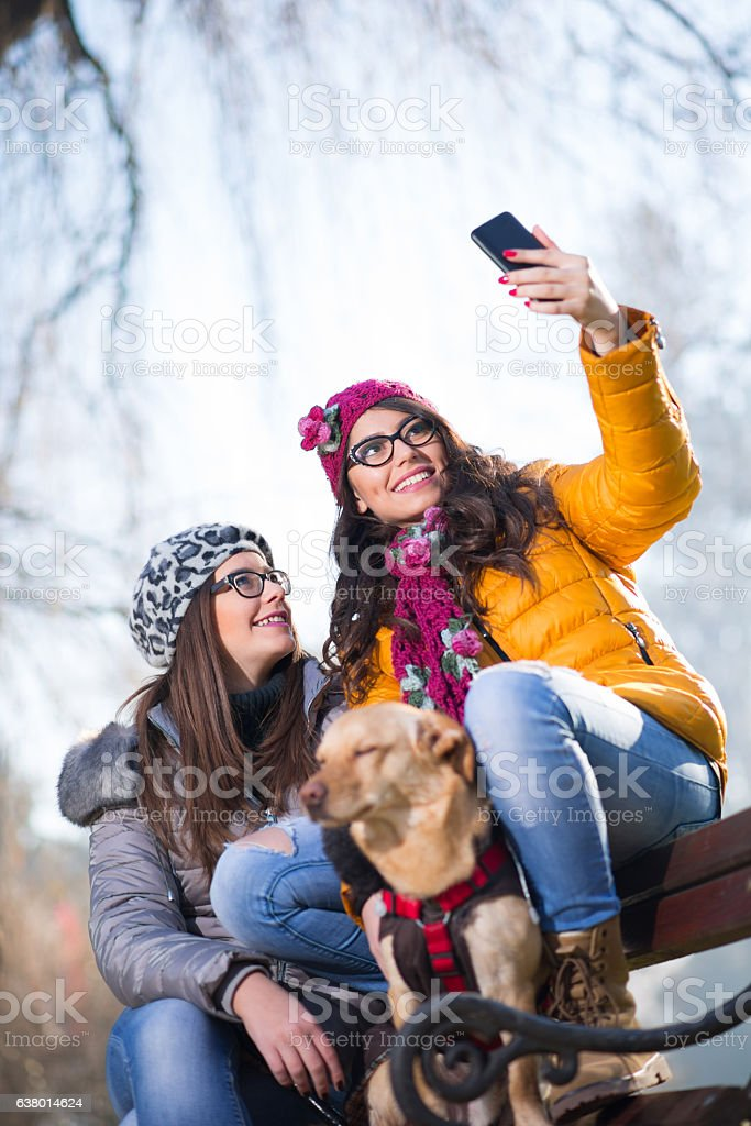 Beautiful and happy girls enjoying in autumn park stock photo