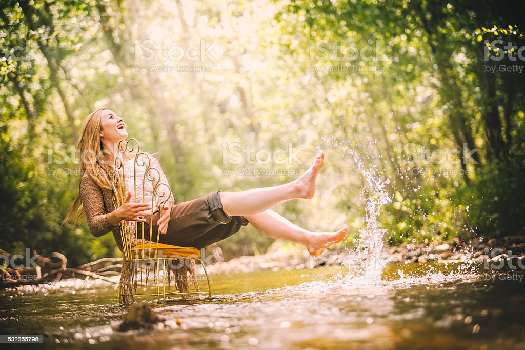 Beautiful And Joyful Young Woman In Nature Splashing Water stock photo