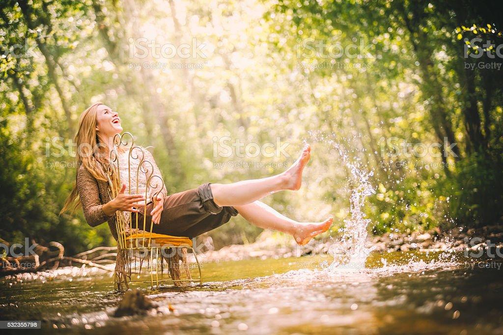 Beautiful And Joyful Young Woman In Nature Splashing Water stock photo