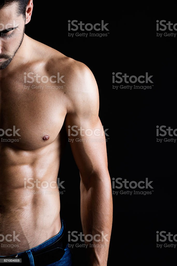 Beautiful and muscular man in dark background. stock photo