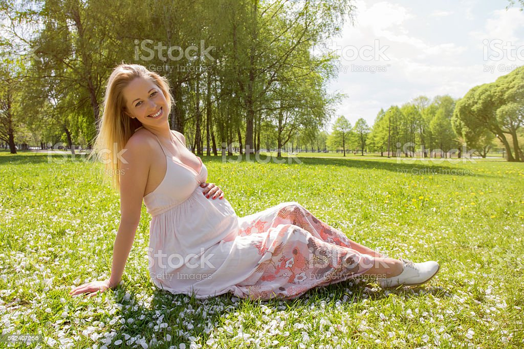 Beautiful and pregnant woman sitting in grass stock photo