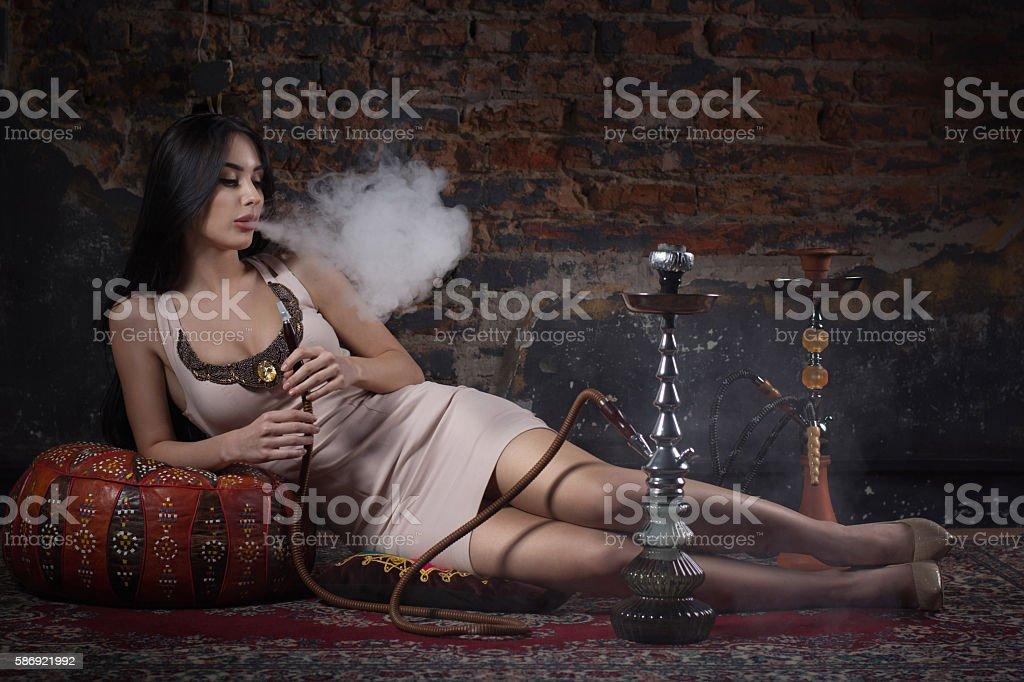 Beautiful and sexy glamorous woman smoking hookah stock photo