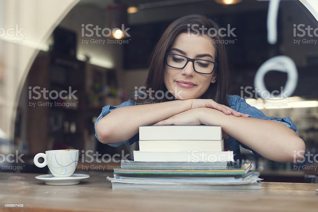 Beautiful and smiling female student at cafe stock photo