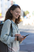 Beautiful and smiling girl looking at her smartphone