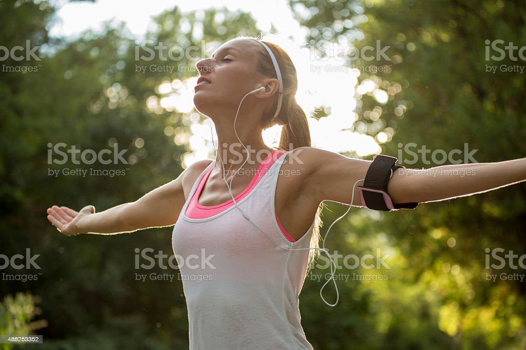Beautiful and sporty young woman arms outsretched for freedom stock photo