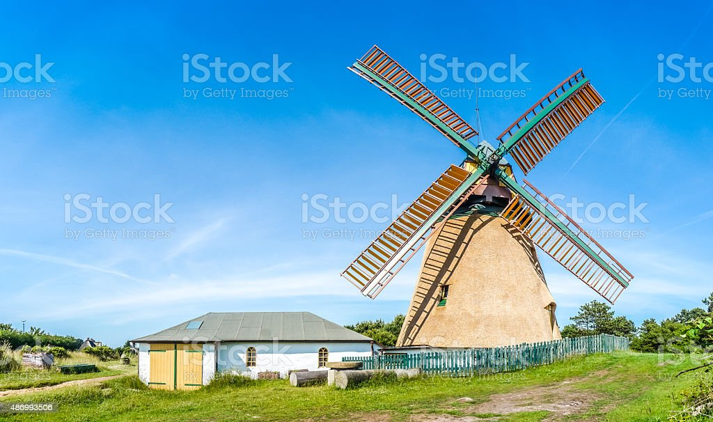 Beautiful and traditional thatched windmill in german north sea village stock photo