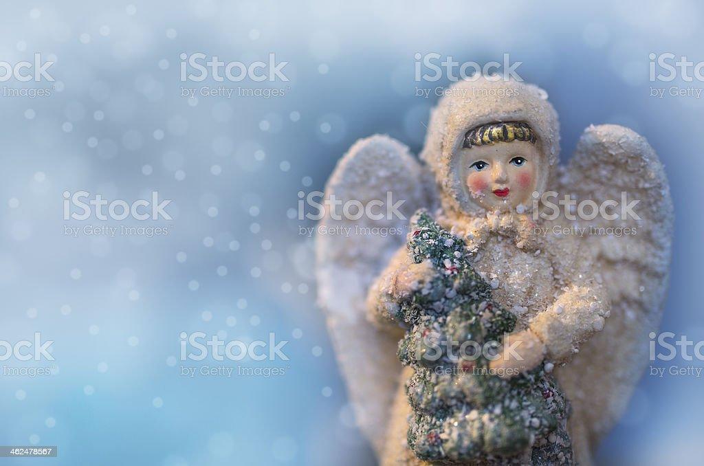 Beautiful angel figurine with Christmas tree and falling snow stock photo