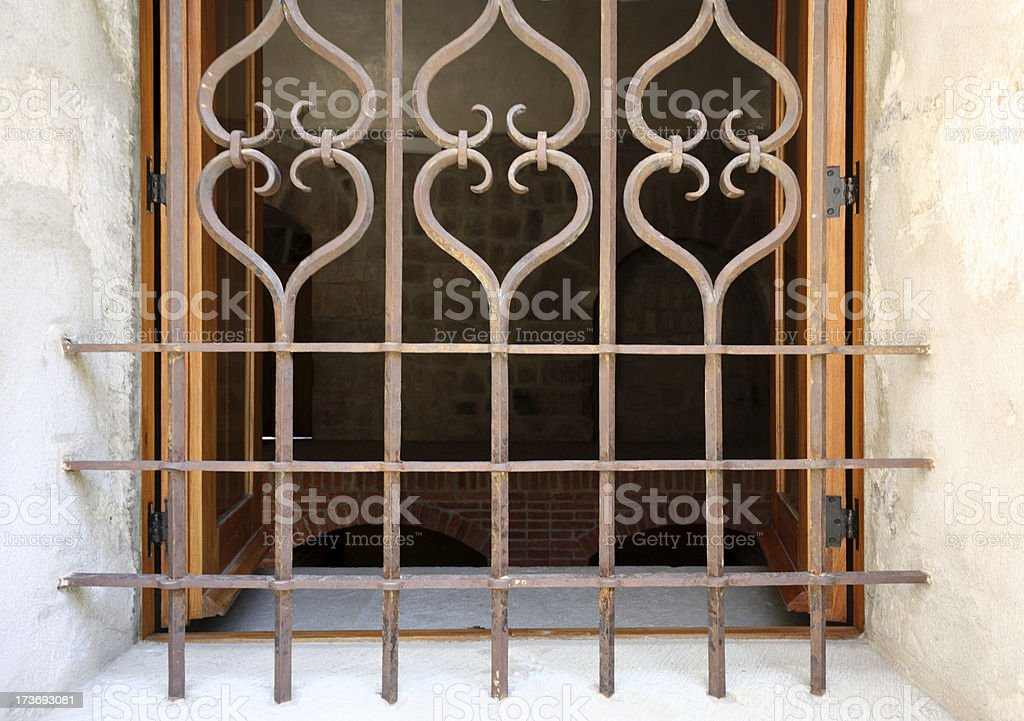 Beautiful antique wrought iron security bars on window royalty-free stock photo