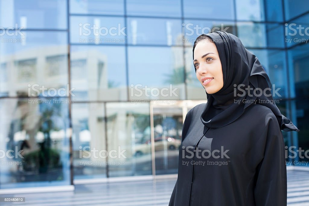 Beautiful arab woman waiting in front of an office building stock photo
