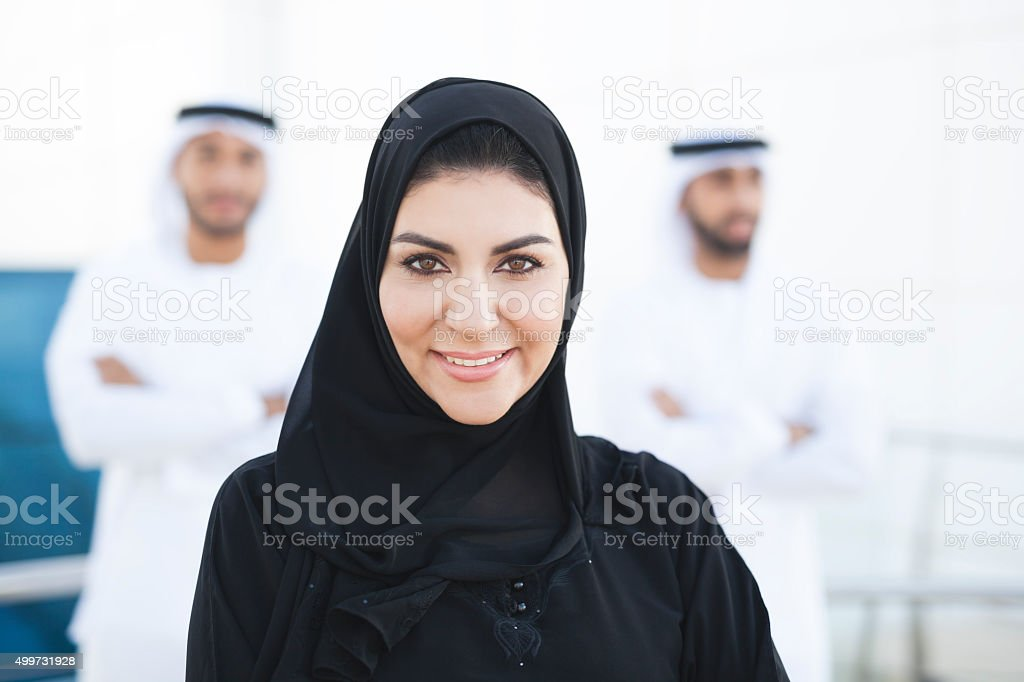 Beautiful Arabian Woman With Two Arab Men Standing Behind stock photo