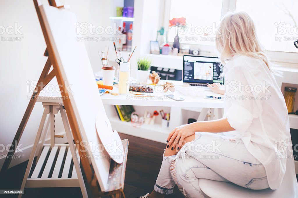 Beautiful artist responding to emails on her laptop stock photo