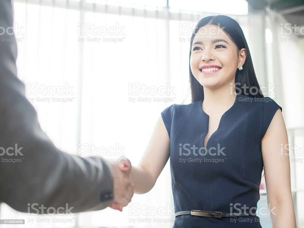 Beautiful Asian businesswoman smiling and shaking hands stock photo