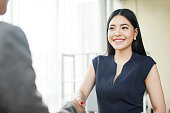 Beautiful Asian businesswoman smiling and shaking hands