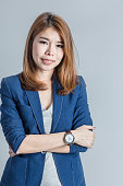 beautiful asian businesswomanwith cute smile isolated on grey ba