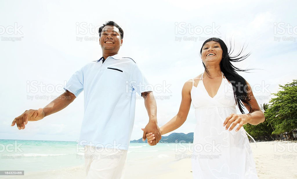 Beautiful Asian couple holding hands at the beach. royalty-free stock photo