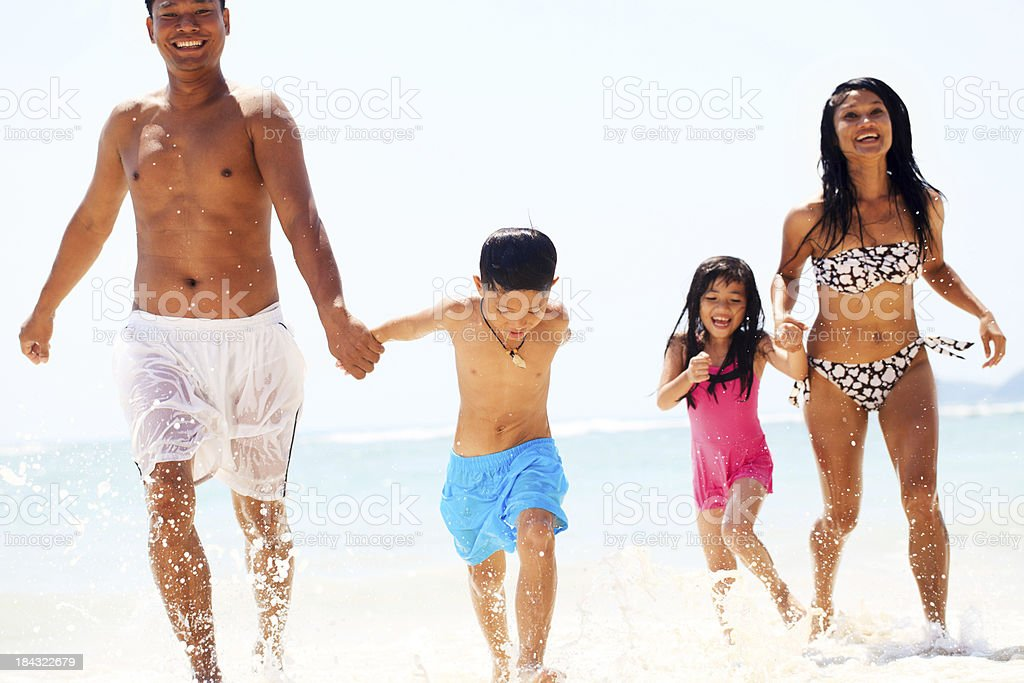 Beautiful Asian family coming out of the water. royalty-free stock photo