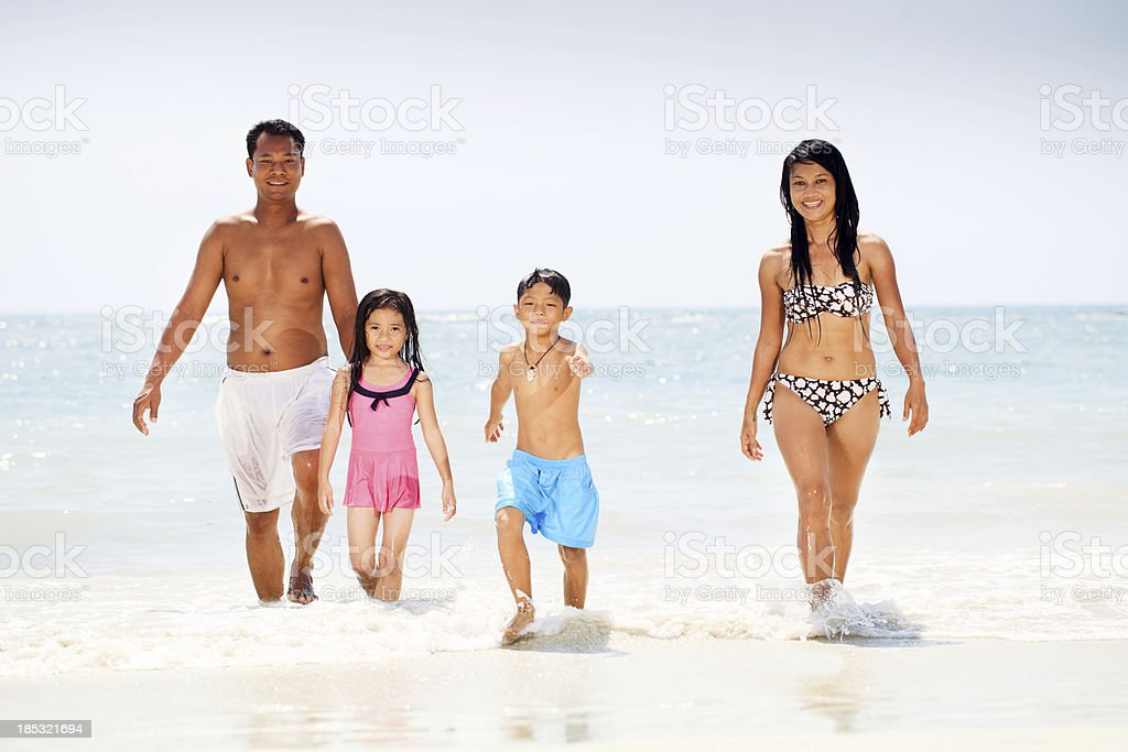 Beautiful Asian family coming out of the water royalty-free stock photo