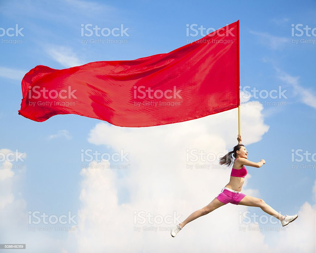 Beautiful Asian female jumping with big red flag stock photo