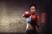 Beautiful asian female training punch with boxing gloves